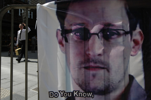 """FILE - In this  June 21, 2013 file photo, a banner supporting Edward Snowden, a former CIA employee who leaked top-secret documents about sweeping U.S. surveillance programs, is displayed at Central, Hong Kong's business district. The Hong Kong government says Snowden wanted by the U.S. for revealing two highly classified surveillance programs has left for a """"third country."""" The South China Morning Post reported Sunday, June 23, 2013 that Snowden was on a plane for Moscow, but that Russia was not his final destination. Snowden has talked of seeking asylum in Iceland. (AP Photo/Kin Cheung, File)"""