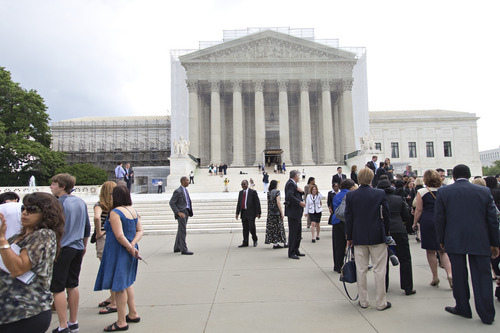 People wait outside the Supreme Court in anticipation of key decisions being announced, on Capitol Hill in Washington, Monday, June 17, 2013. With a week remaining in the current Supreme Court term, several major cases are still outstanding that could have widespread political impact on same-sex marriage, voting rights, and affirmative action. (AP Photo/J. Scott Applewhite)