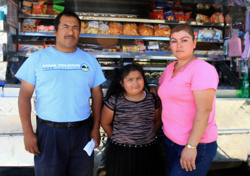 Rick Egan  | The Salt Lake Tribune   Domingo Gonzalez (left) with his 7-year-old daughter Susana and his wife Maritza Gonzalez stand in front of the food truck that the family runs. Domingo faces deportation hearings after he was stopped at the border when returning from a visit to his ailing father.