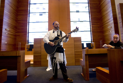 Kim Raff  |  The Salt Lake Tribune Rabbi Joshua Aaronson plays guitar as people arrive for a Shabbat service at Temple Har Shalom in Park City on May 31, 2013. Rabbi Aaronson will be leaving the congregation at the end of the month.