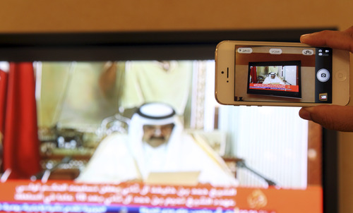 A man prepares to take a picture with his mobile photo of a televised address by Qatar's Emir Sheik  Hamad bin Khalifa Al Thani, in Doha, Qatar,Tuesday, June 25, 2013. Qatar's ruler said Tuesday he has transferred power to the 33-year-old crown prince in an anticipated move that puts a new generation in charge of the Gulf nation's vast energy wealth and rising political influence.  (AP Photo/Osama Faisal)