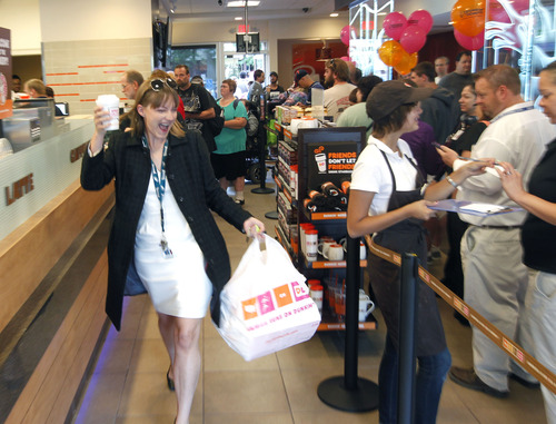 Al Hartmann  |  The Salt Lake Tribune Happy customer leaves the counter with coffee and a big bag of doughnuts at the grand opening of Dunkin' Donuts at 217 E. 400 South on Tuesday, June 25. The Utah franchise, Sizzling Platter, is planning to open up to 23 Dunkin' Donuts outlets along the Wasatch Front and northern Utah during the next five years.