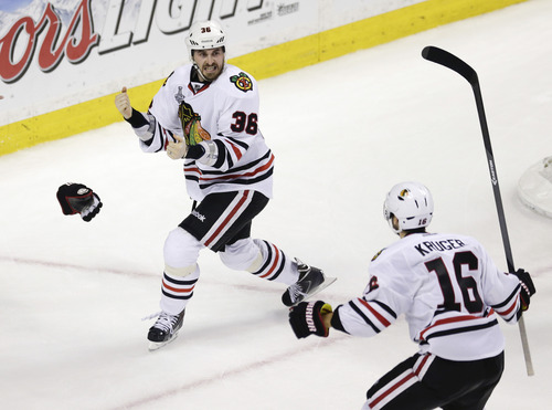 Chicago Blackhawks center Dave Bolland (36) celebrates his game-winning goal against the Boston Bruins with Chicago Blackhawks center Marcus Kruger (16) during the third period in Game 6 of the NHL hockey Stanley Cup Finals, Monday, June 24, 2013, in Boston. The Blackhawks won 3-2. (AP Photo/Charles Krupa)