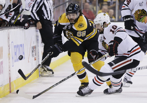 Chicago Blackhawks center Patrick Sharp (10) and Boston Bruins right wing Jaromir Jagr (68), of the Czech Republic, pursue the puck during the first period in Game 6 of the NHL hockey Stanley Cup Finals Monday, June 24, 2013 in Boston. (AP Photo/Elise Amendola)