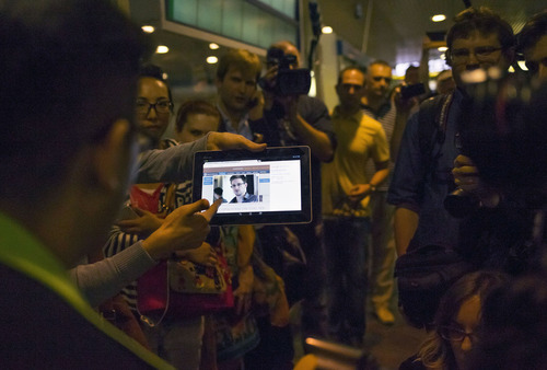 """Journalists show passengers arriving from Hong Kong a tablet with a photo of Edward Snowden, a former CIA employee who leaked top-secret documents about sweeping U.S. surveillance programs, at Sheremetyevo airport, just outside Moscow,  Russia, Sunday, June 23, 2013. The former National Security Agency contractor wanted by the United States for revealing two highly classified surveillance programs has been allowed to leave for a """"third country"""" because a U.S. extradition request did not fully comply with Hong Kong law, the territory's government said Sunday. (AP Photo/Alexander Zemlianichenko)"""