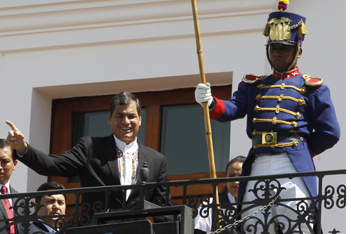"""Ecuador's President Rafael Correa, left, greets passersby from the balcony of the presidential palace during the weekly, The Change of the Guard, in Quito, Ecuador, Monday, June 24, 2013. The Ecuadorian government declared Monday that national sovereignty and universal principles of human rights would govern their decision on granting asylum to Edward Snowden, powerful hints that the former National Security Agency contractor is welcome despite potential repercussions from Washington. Correa said on Twitter that """"we will take the decision that we feel most suitable, with absolute sovereignty."""" AP Photo/Dolores Ochoa)"""