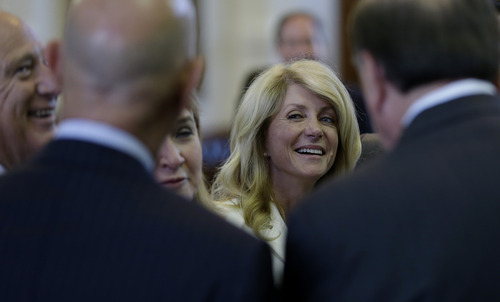 Sen. Wendy Davis, D-Fort Worth, center, talks with fellow senators during a recess, Monday, June 24, 2013, in Austin, Texas. Senate democrats are trying to hold off on a  bill that  would ban abortion after 20 weeks of pregnancy and force many clinics that perform the procedure to upgrade their facilities and be classified as ambulatory surgical centers.  (AP Photo/Eric Gay)
