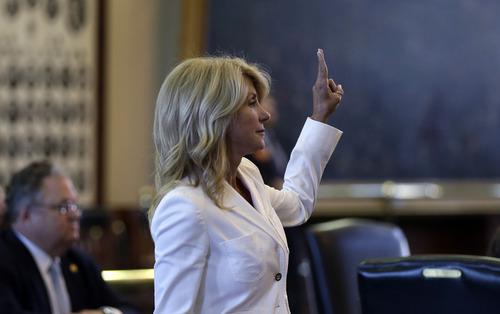 Sen. Wendy Davis, D-Fort Worth, holds up two fingers to cast a no vote to bring an abortion bill to the floor early for debate, Monday, June 24, 2013, in Austin, Texas. The bill would ban abortion after 20 weeks of pregnancy and force many clinics that perform the procedure to upgrade their facilities and be classified as ambulatory surgical centers. (AP Photo/Eric Gay)
