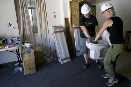 Rick Egan  | The Salt Lake Tribune   Jaron Noyce and Teresa Marsco, volunteers from OC Tanner, are remove a toilet from the old LDS church on 400 East and 100 South in Salt Lake, Wednesday, June 26, 2013. The American Cancer Society has donated a retired LDS Church building to Habitat for Humanity, which will eventually be a Hope Lodge for cancer patients.