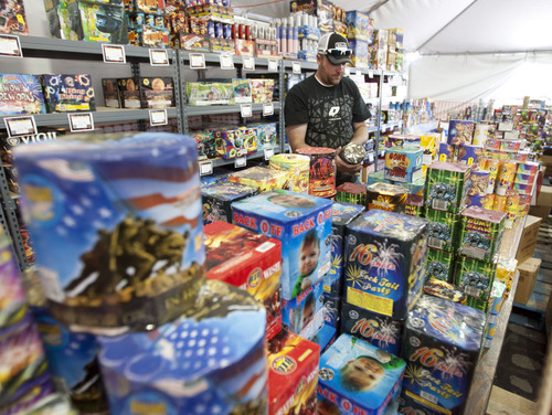 Steve Griffin | The Salt Lake Tribune   Brian Nelson,  owner of Fireworks Frenzy, stocks his fireworks tent at 580 S. State St. in Clearfield on Tuesday June 25, 2013.
