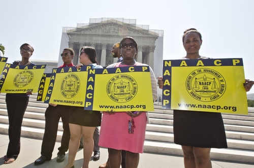 Representatives from the NAACP Legal Defense Fund stand outside the Supreme Court in Washington, Tuesday, June 25, 2013, awaiting a decision in Shelby County v. Holder, a voting rights case in Alabama. The Supreme Court says a key provision of the landmark Voting Rights Act cannot be enforced until Congress comes up with a new way of determining which states and localities require close federal monitoring of elections.    (AP Photo/J. Scott Applewhite)