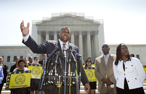 Ryan P. Haygood, director of the NAACP Legal Defense Fund, talks outside the Supreme Court in Washington, Tuesday, June 25, 2013, about the Shelby County v. Holder, a voting rights case in Alabama. Charles White, the national field director for the NAACP is second from right and Sherrilyn Ifill, president of the NAACP Legal Defense Fund is at right. The Supreme Court says a key provision of the landmark Voting Rights Act cannot be enforced until Congress comes up with a new way of determining which states and localities require close federal monitoring of elections. (AP Photo/J. Scott Applewhite)