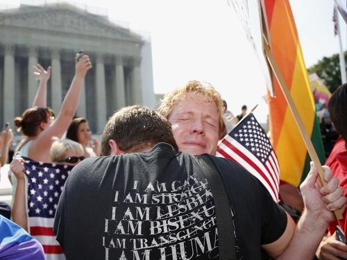 Michael Knaapen, left, and his husband John Becker, right, embrace outside the Supreme Court in Washington, Wednesday, June 26, 2013 after the court struck down a federal provision denying benefits to legally married gay couples. (AP Photo/Charles Dharapak)