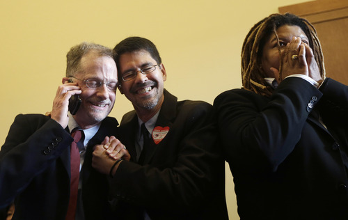 John Lewis, left, and his partner Stuart Gaffney embrace as they react next to Andrea Shorter after the Supreme Court decision at the office of San Francisco Mayor Ed Lee at City Hall in San Francisco, Wednesday, June 26, 2013.  The Supreme Court on Wednesday struck down a provision of a U.S. law denying federal benefits to married gay couples and cleared the way for the resumption of same-sex marriage in the state of California. The justices issued two 5-4 rulings in their final session of the term. One decision wiped away part of a federal anti-gay marriage law that has kept legally married same-sex couples from receiving tax, health and pension benefits. The other was a technical legal ruling that said nothing at all about same-sex marriage, but left in place a trial court's declaration that California's Proposition 8 is unconstitutional. (AP Photo/Jeff Chiu)