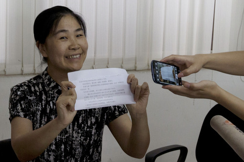 Chu Lixiang, director of Huairou district workers union, holds up a letter of settlement during a press conference held at a medical supply plant in Beijing, China, Thursday, June 27, 2013. An American boss of the factory detained nearly a week by his company's Chinese workers left the Beijing factory Thursday after he and a union representative said the two sides reached agreement in a pay dispute. (AP Photo/Ng Han Guan)