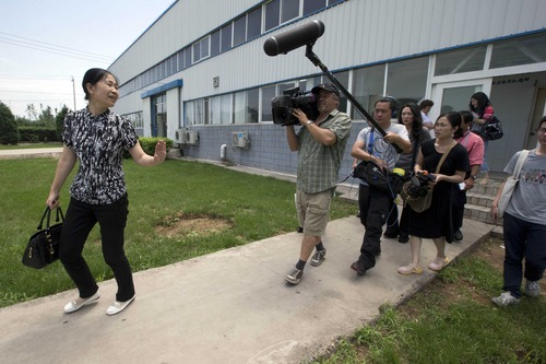 Chu Lixiang, director of Huairou district workers union, is followed by journalists after a press conference held at a medical supply plant in Beijing, China, Thursday, June 27, 2013. An American boss of the factory detained nearly a week by his company's Chinese workers left the Beijing factory Thursday after he and a union representative said the two sides reached agreement in a pay dispute. (AP Photo/Ng Han Guan)