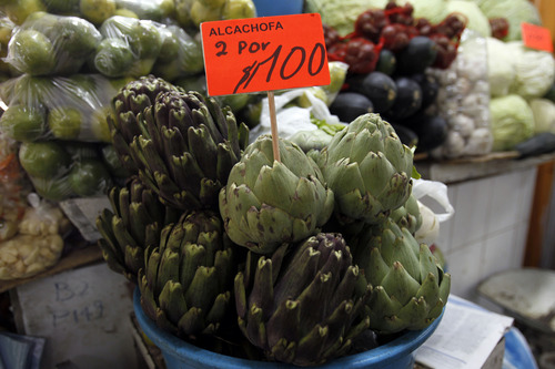 """Artichokes sit for sale, with a sign that reads """"Two for $1 dollar"""" at a market in downtown Quito, Ecuador, Thursday, June 27, 2013. Unlike with China, Russia or Cuba, countries where the U.S. has relatively few tools to force Edward Snowden's handover, the Obama administration could swiftly hit Ecuador in the pocketbook by denying reduced tariffs on cut flowers, artichokes and broccoli if it grants Snowden's request for asylum. Those represent hundreds of millions of dollars in annual exports for this country where nearly half of foreign trade depends on the U.S. (AP Photo/Dolores Ochoa)"""