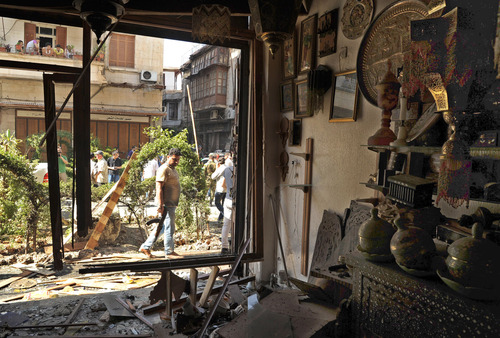 This photo released by the Syrian official news agency SANA, shows a Syrian security agent looking at a damaged antique shop after a blast struck in the vicinity of the Greek Orthodox Virgin Mary Church in the predominantly Christian neighborhood of Bab Sharqi in central Damascus, Syria, Thursday, June 27, 2013. A suicide attacker blew himself up near one of the main churches in the Syrian capital Thursday, killing several people, state-run TV said. (AP Photo/SANA)