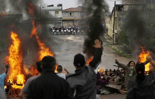 Residents shout slogans against police as they set a roadblock on fire to fight their eviction from the Parque Sao Rafael neighborhood in Sao Paulo, Brazil, Thursday, June 27, 2013.  Police are evicting more than 100 families from this private property which has been illegally occupied for about one year. The land is located far away from infrastructure related to the upcoming World Cup and Olympic games. (AP Photo/Nelson Antoine)