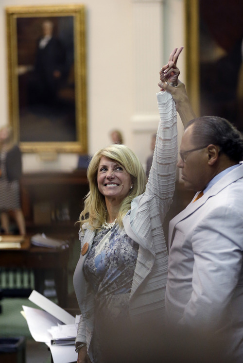 Sen. Wendy Davis, D-Fort Worth, left, who tries to filibuster an abortion bill, reacts as time expires, Wednesday, June 26, 2013, in Austin, Texas. Amid the deafening roar of abortion rights supporters, Texas Republicans huddled around the Senate podium to pass new abortion restrictions, but whether the vote was cast before or after midnight is in dispute. If signed into law, the measures would close almost every abortion clinic in Texas.  (AP Photo/Eric Gay)