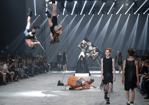 Models wear creations by fashion designer Rick Owens as part of his men's fashion Spring-Summer 2014 collection, presented Thursday, June 27, 2013 in Paris, as Estonian metal/punk band Winny Puhh perform live, suspended by their feet . (AP Photo/Francois Mori)