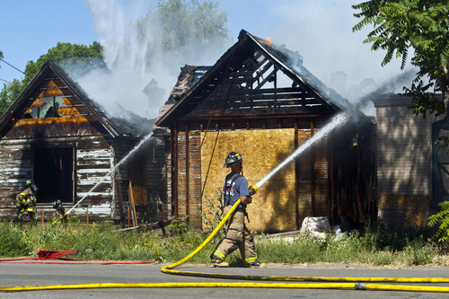 Chris Detrick  |  The Salt Lake Tribune Salt Lake City firefighters work at dousing two abandoned homes that are on fire near 950 South 400 West Thursday June 27, 2013.