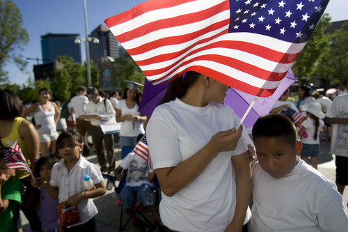 Kim Raff     The Salt Lake Tribune (middle) Maria Miranda waves a flag during the Campaign for Citizenship prayer vigil at the Wallace Bennett Federal Building in Salt Lake City on June 27, 2013.  This event is one of many held around the country to encourage a path to citizenship for undocumented Americans.