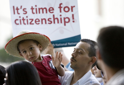 Kim Raff     The Salt Lake Tribune (left) Josue and his father (right) Javier Vega sing along to a song during the Campaign for Citizenship prayer vigil at the Wallace Bennett Federal Building in Salt Lake City on June 27, 2013. This event is one of many held around the country to encourage a path to citizenship for undocumented Americans.