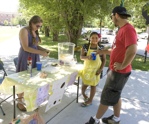 Paul Fraughton  |   The Salt Lake Tribune Parker Ellison stops for a cold lemonade at Maya Johnson's, age 9, and Chelsea Hoyt's lemonade and cookie stand on the corner of South Temple and University Street.                      Thursday, June 27, 2013