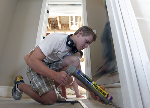Al Hartmann  |  The Salt Lake Tribune Spartan House built from the ground up by Murray High School students is nearly finished. Students are laying carpet and preparing final touches for an open house.  Jake Brown calks down some tacking in preparation for laying carpet.