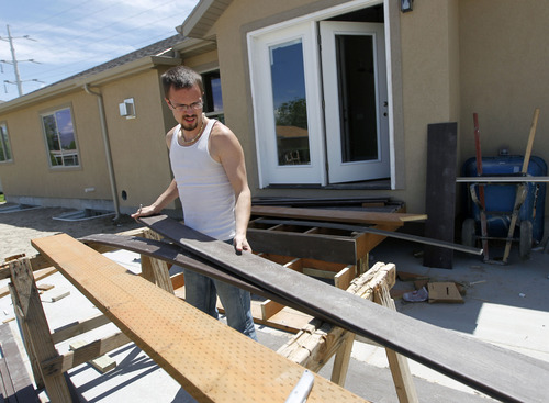 Al Hartmann  |  The Salt Lake Tribune Spartan House built from the ground up by Murray High School students is nearly finished.   Students are laying carpet and preparing final touches for an open house.  Aaron Hamilton cuts tyvek for a backdoor deck Wednesday May 22.