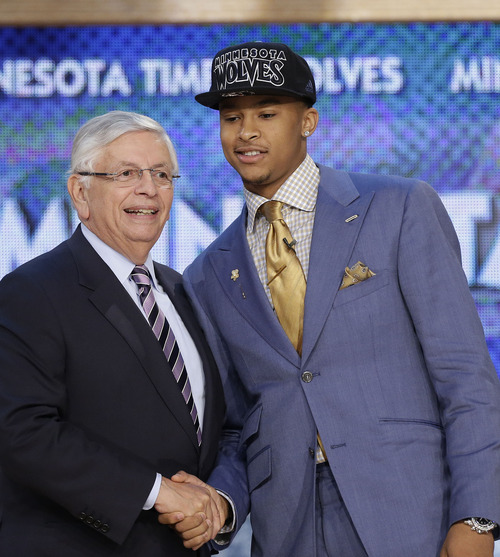 CORRECTS TEAM THAT DRAFTED BURKE TO THE MINNESOTA TIMBERWOLVES - NBA Commissioner David Stern, left, shakes hands with Michigan's Trey Burke, who was selected by the Minnesota Timberwolves in the first round of the NBA basketball draft, Thursday, June 27, 2013, in New York. (AP Photo/Kathy Willens)