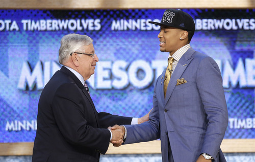 NBA Commissioner David Stern, left, shakes hands with Michigan's Trey Burke, who was selected by the Minnesota Timberwolves in the first round of the NBA basketball draft, Thursday, June 27, 2013, in New York. (AP Photo/Kathy Willens)