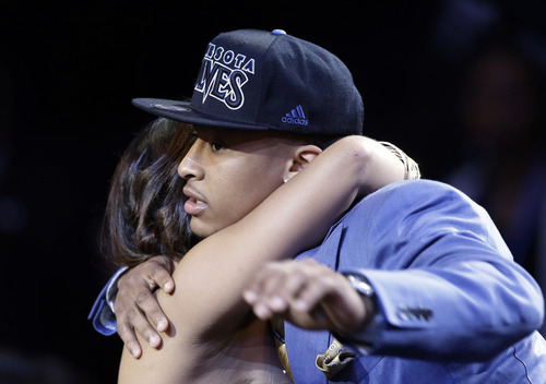 Michigan's Trey Burke receives a hug after being selected by the Minnesota Timberwolves in the first round of the NBA basketball draft, Thursday, June 27, 2013, in New York. (AP Photo/Kathy Willens)