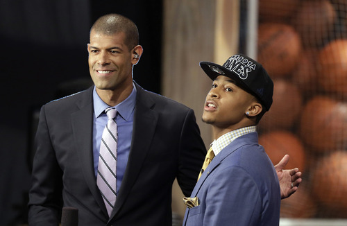 CORRECTS TEAM THAT DRAFTED BURKE TO THE MINNESOTA TIMBERWOLVES - Michigan's Trey Burke, right, is interviewed by Miami Heat's Shane Battier after being selected by the Minnesota Timberwolves in the first round of the NBA basketball draft, Thursday, June 27, 2013, in New York. (AP Photo/Kathy Willens)
