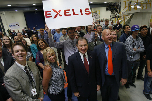Scott Sommerdorf   |  The Salt Lake Tribune Gov. Gary Herbert, center, and Mike Blair, V.P. and general manager of Exelis Aerostructures, at right in orange tie, pose for a photo with newly hired Exelis employees and other sub-contractors, illustrating the job growth announced at a press conference at Excelis Aerostructures. Herbert's goal of creating 100,000 jobs in 1,000 days is on track midway thru the challenge. The private sector has already created 63,600 jobs. In his 2012 State of the State address, Herbert challenged the private sector to create 100,000 jobs in 1,000 days.