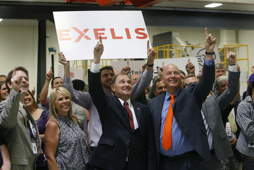 Scott Sommerdorf   |  The Salt Lake Tribune Gov. Gary Herbert, center, and Mike Blair, V.P. and general manager of Exelis Aerostructures, at right in orange tie, pose for a photo illustrating the job growth announced at a press conference at Excelis Aerostructures. Herbert's goal of creating 100,000 jobs in 1,000 days is on track midway thru the challenge. The private sector has already created 63,600 jobs. In Herbert's 2012 State of the State address, he challenged the private sector to create 100,000 jobs in 1,000 days.