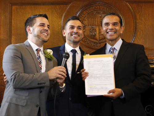 """Jeff Zarrillo, left, and Paul Katami, center, pose for photos after being married by Los Angeles Mayor Antonio Villaraigosa, Friday June 28, 2013 at City Hall in Los Angeles. A three-judge panel of the 9th U.S. Circuit Court of Appeals issued a brief order Friday afternoon dissolving, """"effective immediately,"""" a stay it imposed on gay marriages while the lawsuit challenging the ban advanced through the courts. (AP Photo/Damian Dovarganes)"""