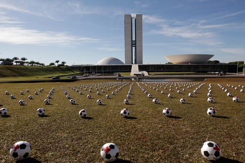 Soccer balls representing lawmakers lay in rows outside Congress as part of a protest against spending on the Confederations Cup soccer tournament in Brasilia, Brazil, Wednesday, June 26, 2013. The wave of protests that hit Brazil on June 17 began as opposition to transportation fare hikes, then expanded to other causes including anger at high taxes, poor services and high World Cup spending, before coalescing around the issue of rampant government corruption. (AP Photo/Eraldo Peres)
