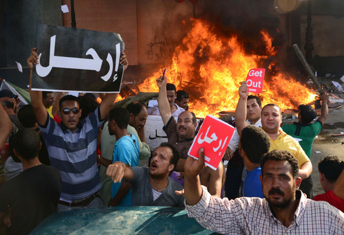 """Opponents of Egypt's Islamist President Mohammed Morsi hold Arabic signs reading """"leave,"""" as fire rages at the Muslim Brotherhood headquarters in Alexandria, Friday, June 28, 2013. Thousands of backers and opponents of Egypt's Islamist president held competing rallies in the capital Friday and new clashes erupted between the two sides in the country's second largest city, Alexandria, in a prelude to massive nationwide protests planned by the opposition this weekend demanding Mohammed Morsi's removal.(AP Photo/Heba Khamis)"""