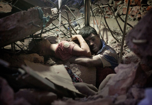 In this Thursday, April 25, 2013 photo, a Bangladeshi man holds on to a woman, both victims of a building collapse, in the debris of Rana Plaza garment factory in Savar near Dhaka, Bangladesh. U.S. President Barack Obama announced Thursday, June 27, 2013, the suspension of U.S. trade privileges for Bangladesh because of concerns over labor rights and worker safety that intensified after hundreds died there in the global garment industry's worst accident. Democratic lawmakers have been pushing for the step since the April 24 collapse of Rana Plaza in Dhaka that killed 1,129 people. (AP Photo/Suman Paul)