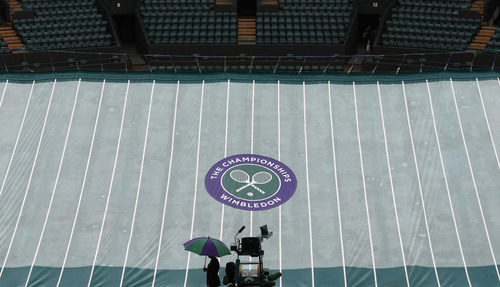 A steward shelters under an umbrella as a court is covered as rain delays the start of play at the All England Lawn Tennis Championships in Wimbledon, London, Friday, June 28, 2013. (AP Photo/Sang Tan)