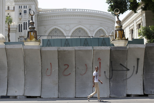 """An Egyptian man walks past graffiti Arabic writing that reads, """"leave"""", on new concrete barricades erected ahead of mass protests against the country's Islamist President Mohammed Morsi that block the entrance of the presidential palace, in Cairo, Egypt, Friday, June 28, 2013. Egypt's main opposition coalition on Thursday rejected the Islamist president's offer for dialogue on reconciliation and said it insists on holding early elections, ratcheting up pressure on Mohammed Morsi just days ahead of planned mass protests seeking his ouster. (AP Photo/Hassan Ammar)"""