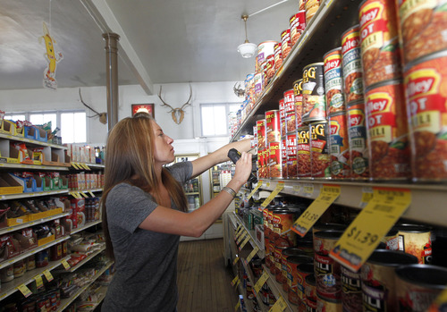 Al Hartmann  |  The Salt Lake Tribune Katie McQueen stocks the shelves of Summit Merc on Coalville's Main Street. It's a traditional small-town general store that carries everything you need. This store is 105 years old and run by the Blonquist family. It has wooden floors, a full grocery section with a white butcher cooler with hand cut meats, hardware section with farm equipment, and work clothes and boots.