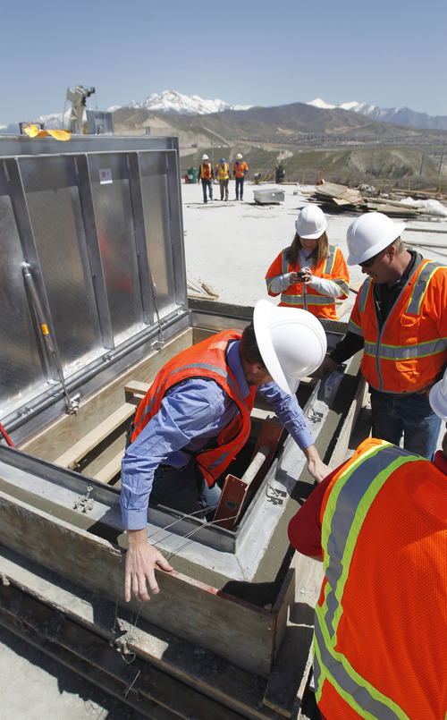 Al Hartmann  |  The Salt Lake  Bluffdale City officials descend a ladder into a 2 million gallon water tank on April 24.  The tank will take water from the new National Security Agency facility at Camp Williams and use it as secondary water for Bluffdale's parks.