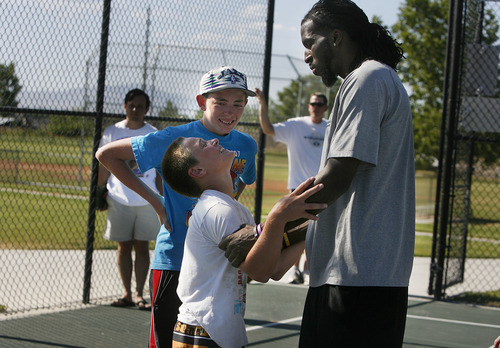 Scott Sommerdorf   |  The Salt Lake Tribune A young Jazz fan jokingly pleads with Jazz player DeMarre Carroll to play on his team during a Jr. Jazz appearance at Reese Park in Brigham City, Friday, June 28, 2013.