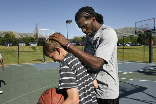 Scott Sommerdorf   |  The Salt Lake Tribune Jazz player DeMarre Carroll congratulates 14 year old Seth Anderson after a good try in a drill as Carroll worked with kids in Brigham City during a Jr. Jazz appearance, Friday, June 28, 2013.