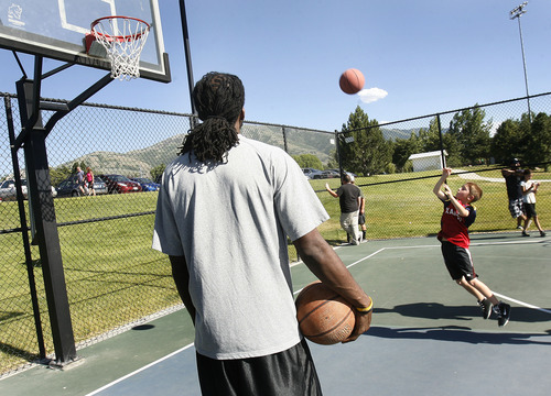 Scott Sommerdorf   |  The Salt Lake Tribune Jazz player DeMarre Carroll watches a young Jazz fan give it his all in Brigham City during a Jr. Jazz appearance, Friday, June 28, 2013.