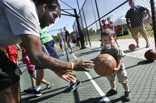 Scott Sommerdorf   |  The Salt Lake Tribune Jazz player DeMarre Carroll takes time to play with 1 year old Wyatt Villafuerte who was at the Jr. Jazz event in Brigham City to watch siblings, Friday, June 28, 2013.