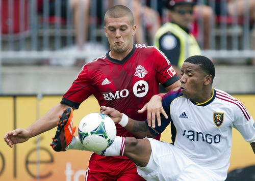 Toronto FC midfielder Ryan Richter, left,  and Real Salt Lake forward Joao Plata battle for the ball during the first half of an MLS soccer game in Toronto on Saturday June 29, 2013. (AP Photo/The Canadian Press, Frank Gunn)